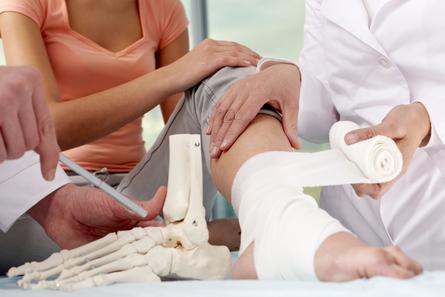 Docteur qui fait un bandage sur une jambe